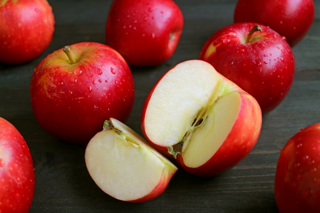 Cut fresh ripe red apple among many whole fruits with water droplets scattered on dark brown wooden table