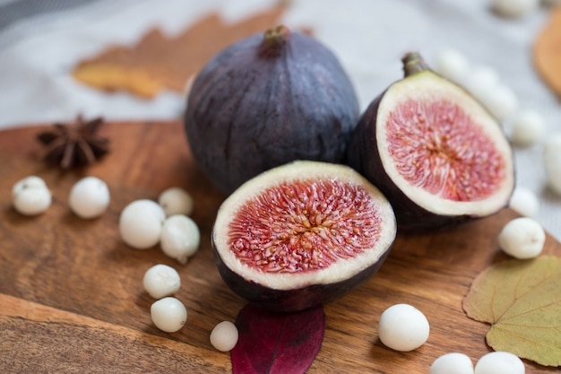 Cut fresh tasty ripe figs on desk with white snow berry, anise, fallen dry leaves, soft focus