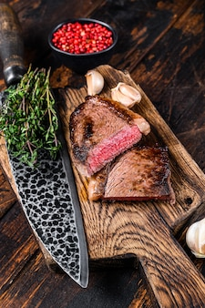 Cut fried rump cap or brazilian picanha beef meat steak on a wooden board. dark wooden background. top view.
