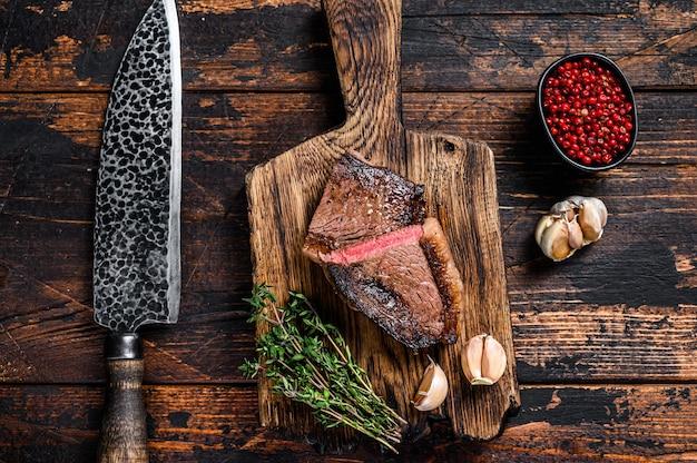 揚げたランプキャップまたはブラジルのピカンハビーフミートステーキを木の板に切ります。暗い木製の背景。上面図。