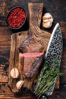Отрежьте жареный огузок или бразильский стейк из говядины пиканья на деревянной доске на деревянном столе. вид сверху.