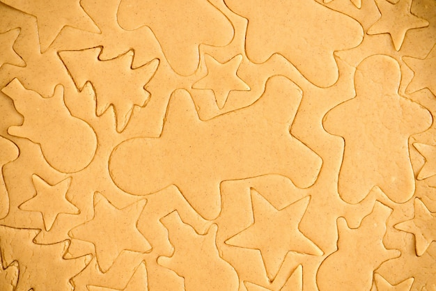 Cut gingerbread out of the dough using a gingerbread mold, top view, raw dough with cinnamon prepared for baking . the pattern on the dough of the figures.