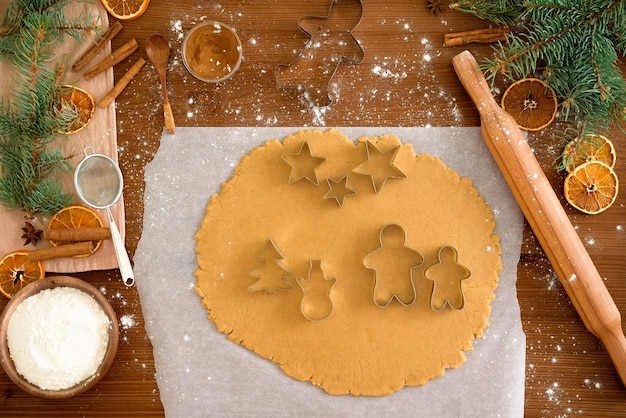 Cut gingerbread out of the dough using a gingerbread mold, top view, rolling pin, cinnamon and dried orange next.