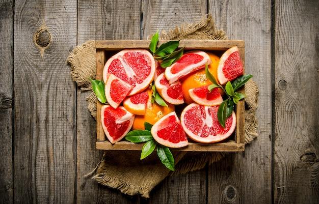木製のテーブルの上に葉を持つ布の古い箱にグレープフルーツをカットします。