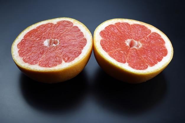 暗い背景にグレープフルーツを切る