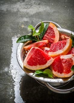 石のテーブルの上の鍋で葉でグレープフルーツをカットします。