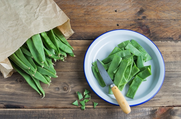 Cut green beans on a plate on a rustic wooden surface. food preparation.