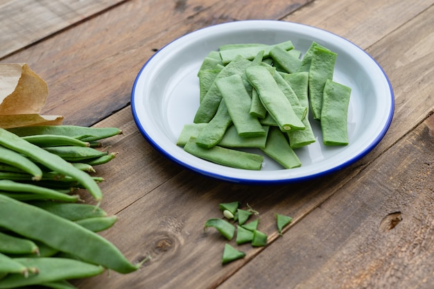 Cut green beans on a plate on a rustic wooden surface. food preparation. Premium Photo