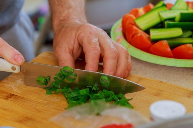 나무 절단 보드에 부엌 칼으로 파를 잘라. 커팅 보드에 신선한 녹색 양파입니다.