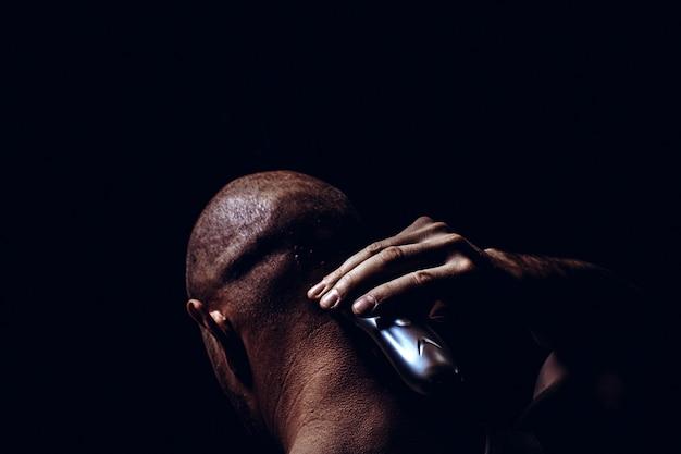 髪をカットし、黒い背景に若い男を剃る。刑務所、背面図で男の側の肖像画を閉じる