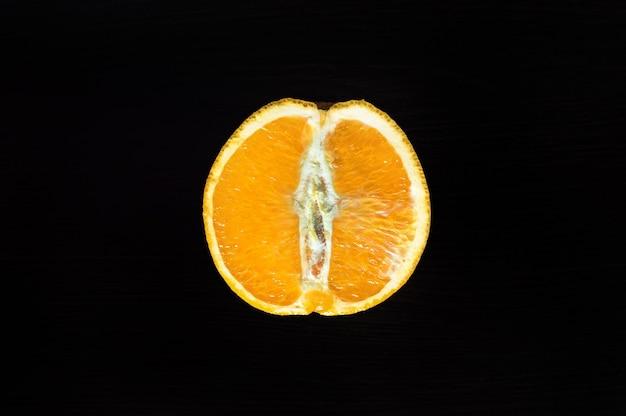 어두운 배경에 있는 나무 테이블에 오렌지 반을 잘라라