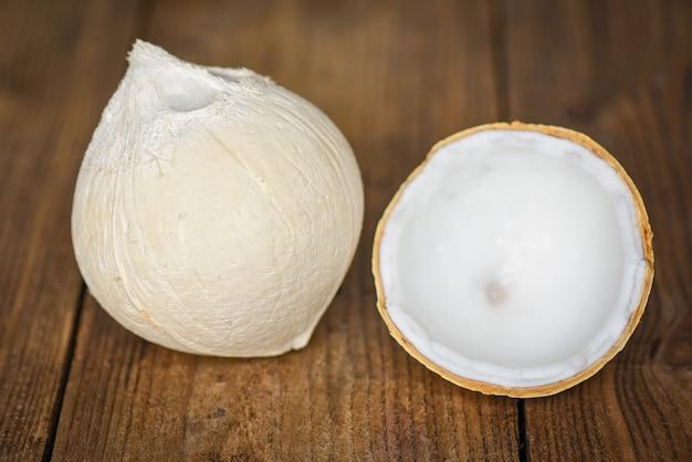 食べ物のために古い木製のテーブルに半分のココナッツと新鮮なココナッツをカットします