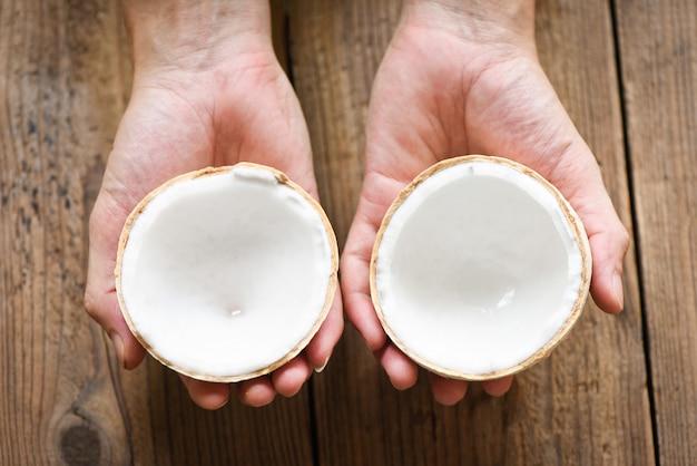 手で半分のココナッツを切り、食べ物のために古い木製のテーブルに新鮮なココナッツを切る