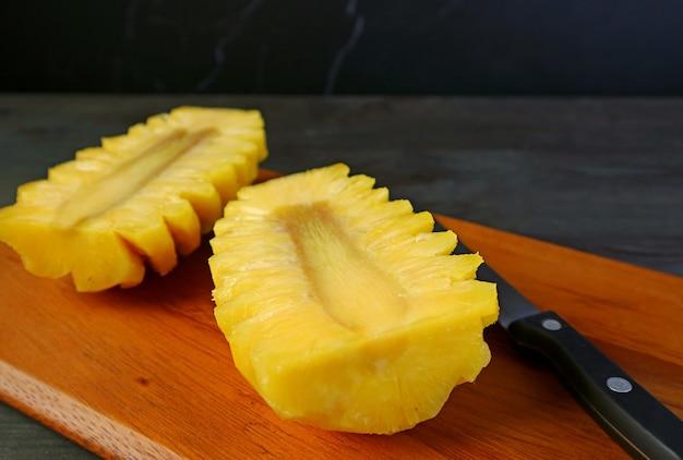 Cut in half of a peeled fresh ripe pineapple on cutting board