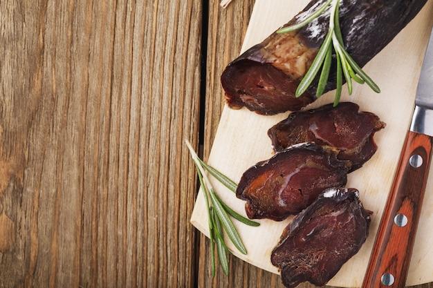 Нарезать домашнюю копченую колбасу на разделочной доске крупным планом, вид сверху