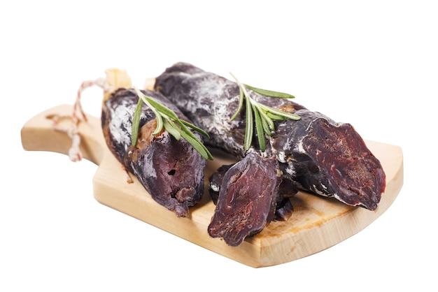 Нарезать домашнюю копченую колбасу на разделочной доске, изолированной на белом фоне