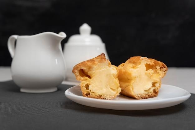Нарезать домашний эклер с начинкой внутри. сладкая выпечка на тарелке. выпечка к чаю.