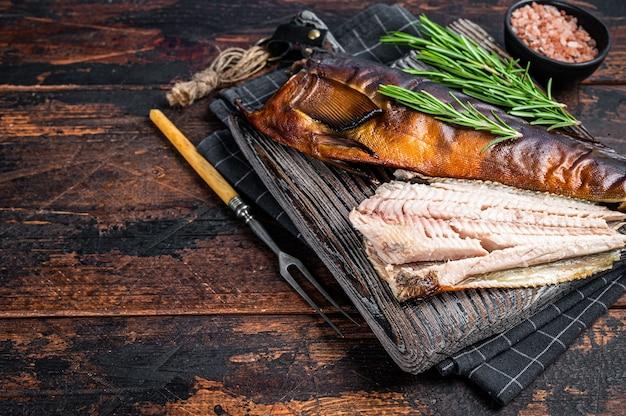 Нарезать рыбу горячего копчения на деревянной доске с розмарином. темный деревянный фон. вид сверху. скопируйте пространство.