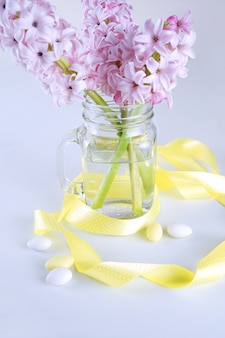 Cut hyacinth flowers in glass vase with yellow ribbon