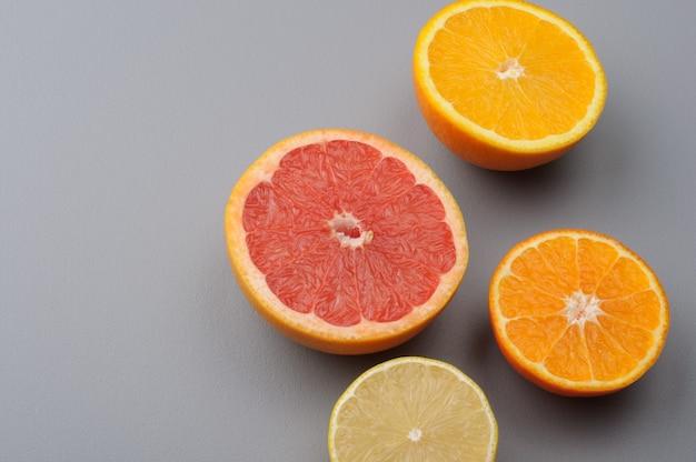 Разрезать пополам свежий лимон, грейпфрут, апельсин, мандарин на сером фоне, вид сверху. ингредиенты цитрусового сока, еда фон