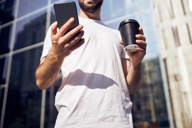스마트 폰과 커피 허리를 들고 남자의 그림 손을 잘라 야외 촬영