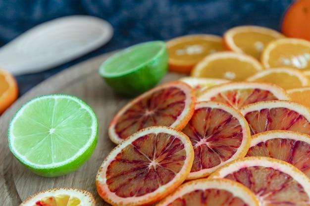 Нарезать круглыми ломтиками разноцветные цитрусовые, апельсин, лайм, кровавый апельсин. темно-синий и деревянный. праздник вкуса и цвета. крупный план.