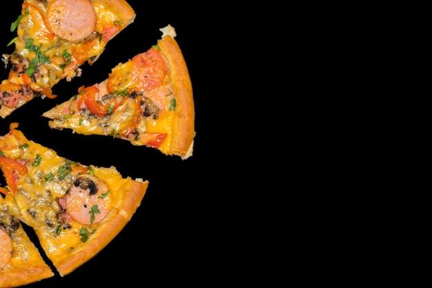 暗い背景にキノコとペパロニを添えたおいしい新鮮なピザをスライスします。上面図。 。黒いテーブルの上のピザ。