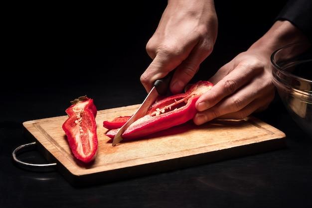 그것을 잘라. 샐러드를 요리하는 동안 고추를 자르고 젊은 망 손 클로즈업