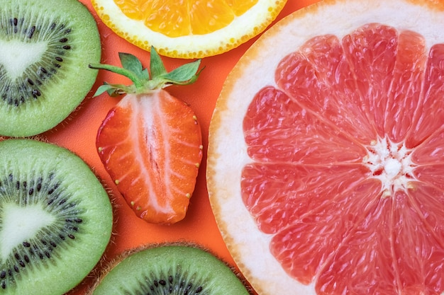 Cut kiwi, grapefruit, strawberry and orange. fruits summer background. citruses bright texture, tropical colorful pattern.