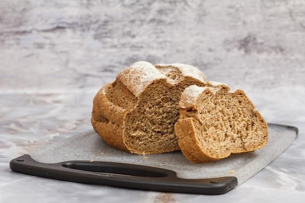 회색 배경이 있는 부엌 책상에 있는 커팅 보드에 빵 한 덩어리를 자른다