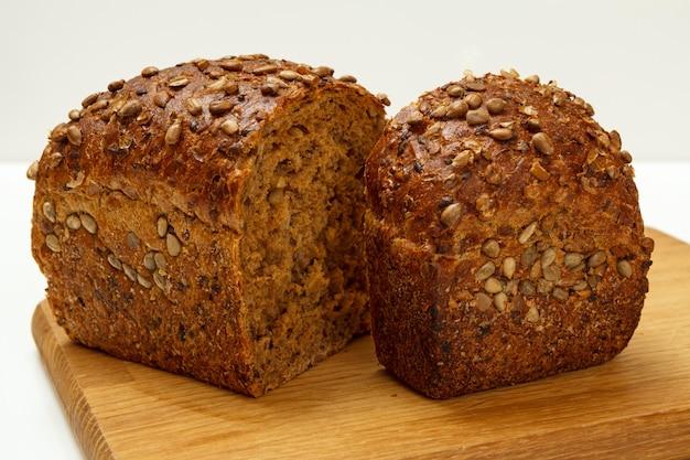 Нарезать буханку ржаного хлеба на деревянной разделочной доске с белой поверхностью.