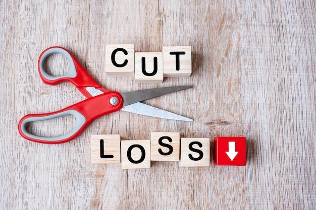테이블 배경에 손실 나무 큐브 블록 및가 위를 잘라. 주식 시장, 위기, 경제 불황 및 위험 사업 개념