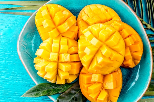 Cut mango on a blue plate