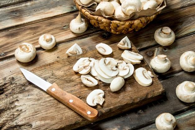まな板の上できのこをナイフで切る。木製のテーブルの上