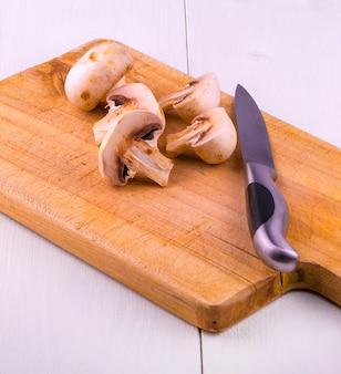 きのこを木の板とナイフで切る。