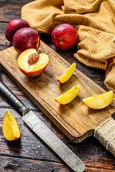 Cut nectarines on a wooden cutting board. wooden background. top view.