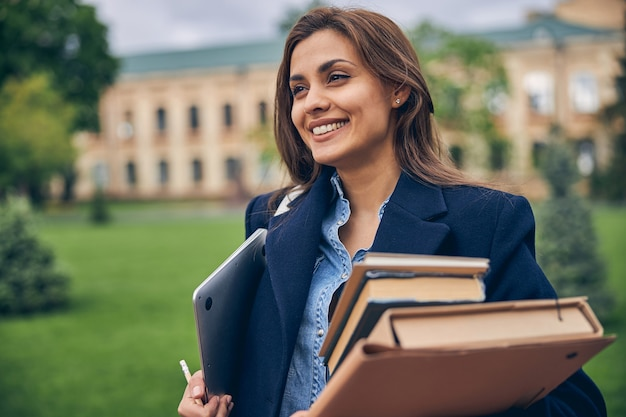 책과 노트북으로 대학 근처에 머무르는 아름다운 학생의 사진을 잘라냅니다.