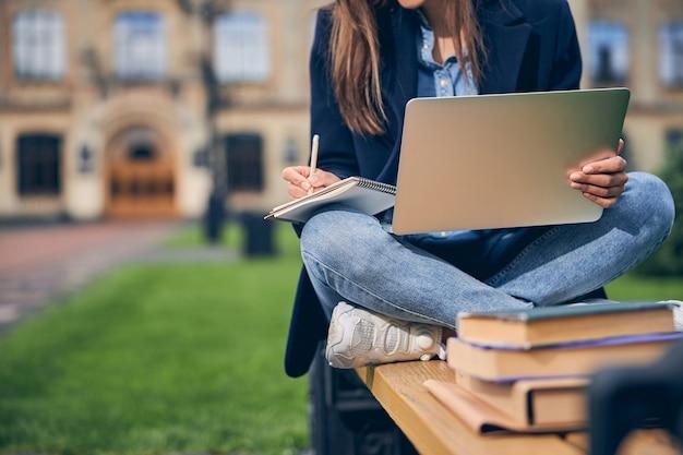 노트북에서 쓰는 동안 책과 함께 벤치에 앉아 갈색 머리 학생의 사진을 잘라
