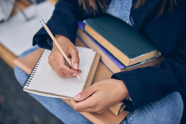 노트북에 연필로 앉아서 쓰는 청바지에 여성의 사진을 잘라