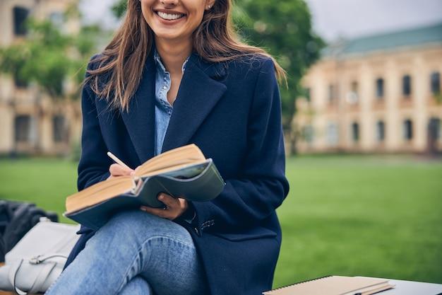 긴 머리가 밖에 앉아 연필로 노트북을 들고 웃고있는 여성의 사진을 잘라냅니다.