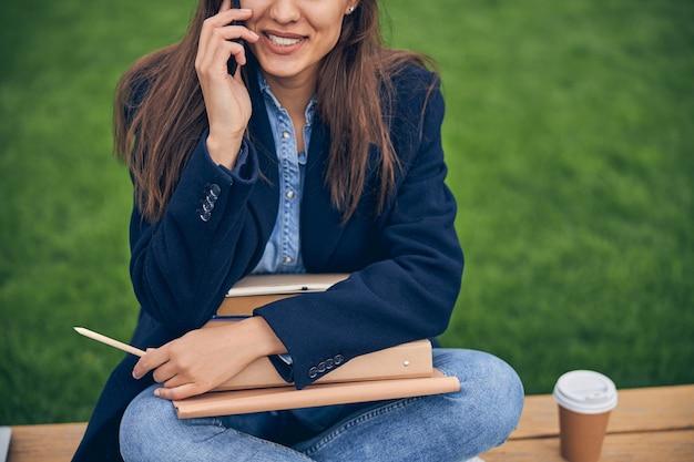 밖에서 전화로 이야기하는 동안 검은 머리를 가진 웃는 아가씨의 사진을 잘라