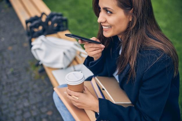 전화로 이야기하는 동안 벤치에 앉아 웃는 젊은 아가씨의 사진을 잘라