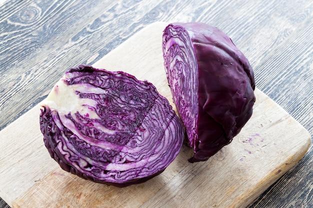 Разрежьте на разделочной доске кочан красной капусты, чтобы приготовить красивый салат, крупным планом