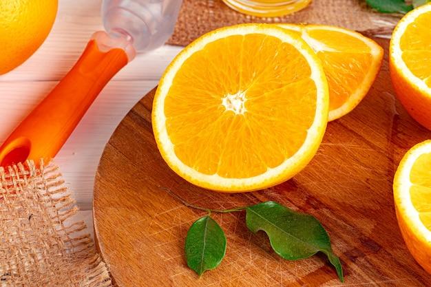 テーブルの上の木の板にオレンジを切る