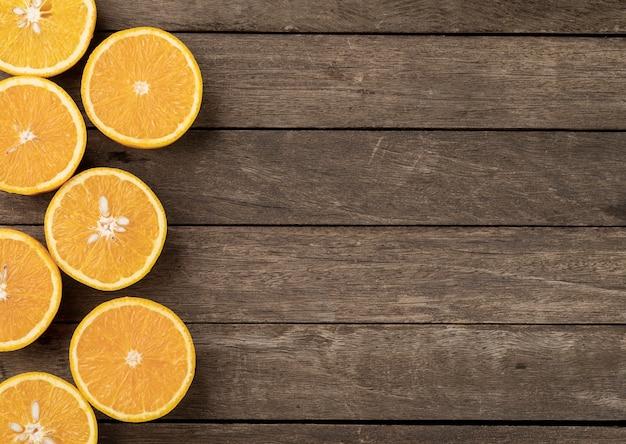 コピースペースのある木製のテーブルの上にオレンジをカットします。