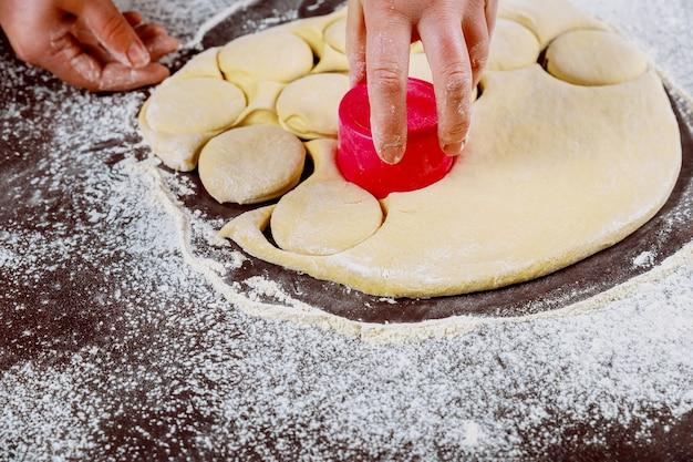 Вырезать кружочки из теста для приготовления сладких булочек, доунутов.