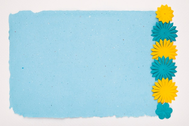 Cut out flowers border on blue paper over white backdrop