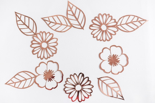 Cut out golden flowers and leaves on white background