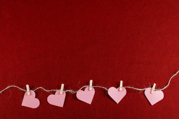 Вырезать бумажные сердца на веревке