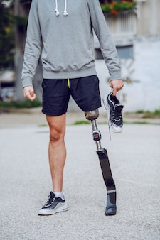 Cut out picture of caucasian handicapped sporty man standing outdoors with sneaker in hand.